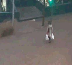 Леди пытается пересечь затопленную улицу.