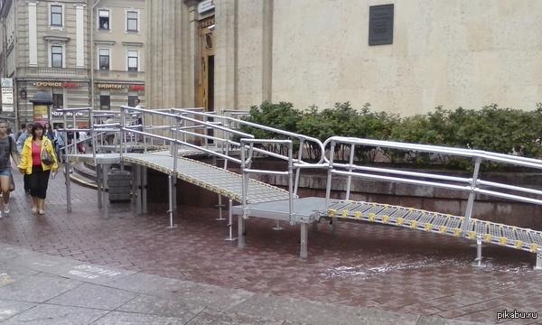 Дорогу инвалидами! Теперь человеку с коляской предлагается пройти такой лабиринт для того, чтобы спуститься на землю из вестибюля метро, а у пешеходов забрали половину тротуара.